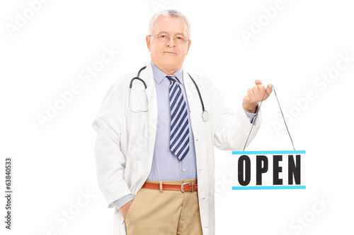 Mature doctor holding an open sign