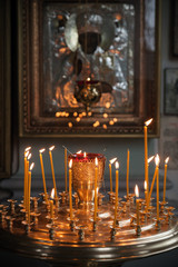 Candles are lit in a dark Orthodox Church above ancient icon
