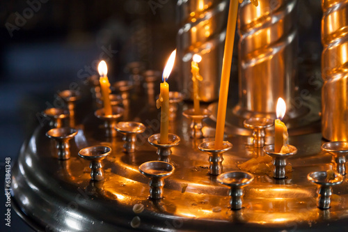 Small candles are lit in a dark Orthodox Church