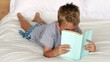 Little boy reading on bed