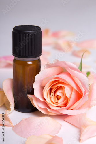 close up of essential oil and rose petals over grey