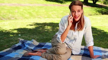 Pretty blonde in the park chatting on the phone