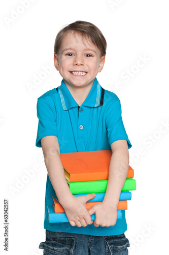 Laughing little boy with books