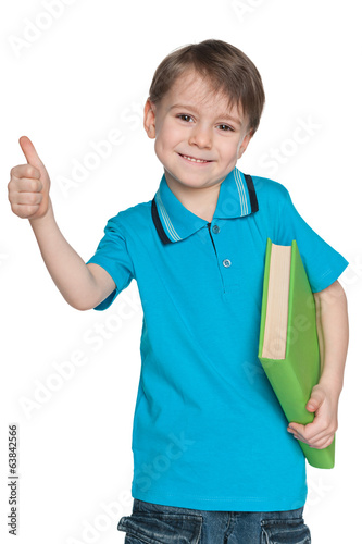 Little boy with book holds his thumb up