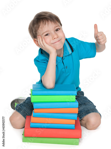 Sitting near the books cheerful boy