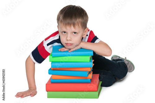 Sad little boy with books