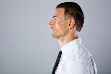 Profile of businessman wearing shirt and tie over gray backround