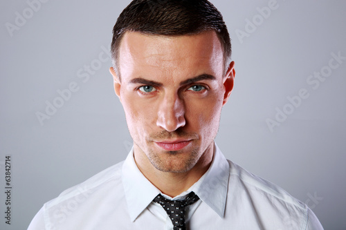 Portrait of a confident businessman over gray background