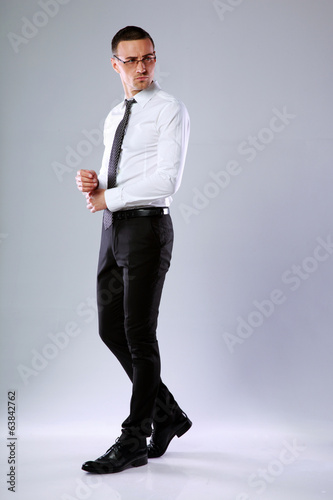 Full-length portrait of a pensive businessman on gray background
