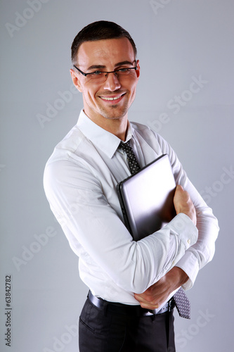 Happy businessman standing with laptop over gray background