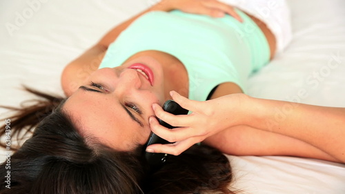 Pretty brunette lying on bed talking on phone