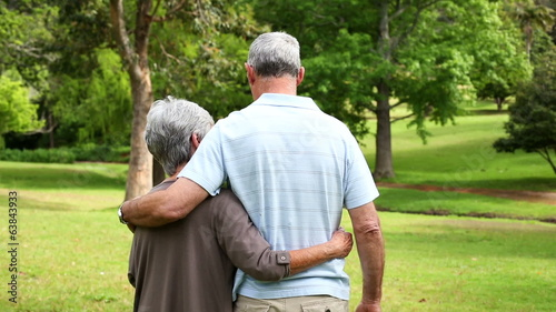 Retired couple standing in the park together