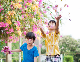Little sibling boy throw flowers in to the air