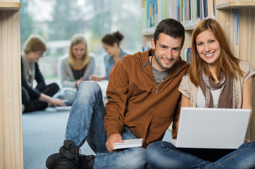 Smiling college students with laptop in library
