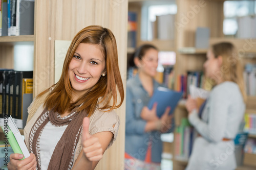Student showing thumb up in library