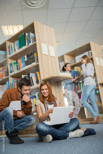 Classmates studying together on laptop in library