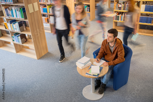 Student writing notes in library blur motion