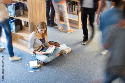 Student sitting floor in library blur motion