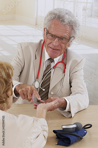 physiotherapist examining a senior woman's wrist
