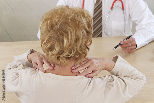 Mature woman holding her neck and talking with   doctor.