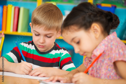 Two little children drawing at kindergarten