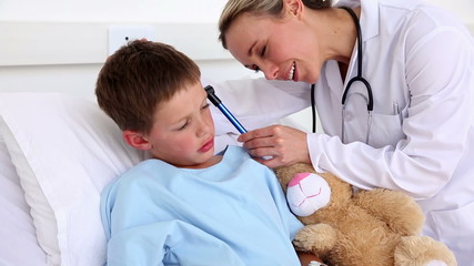 Doctor checking the ears of little sick boy sitting in bed