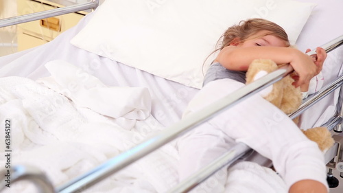Little girl lying in hospital bed