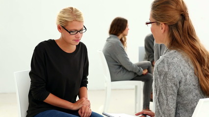 Group sitting in a circle with therapist talking to girl