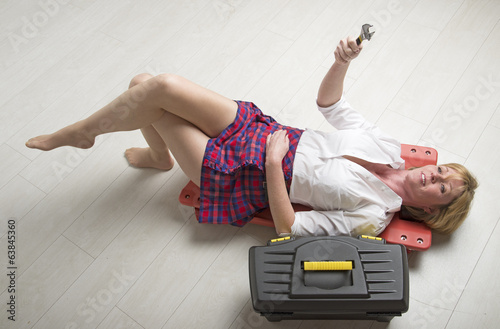 Woman using a crawler and holding a spanner