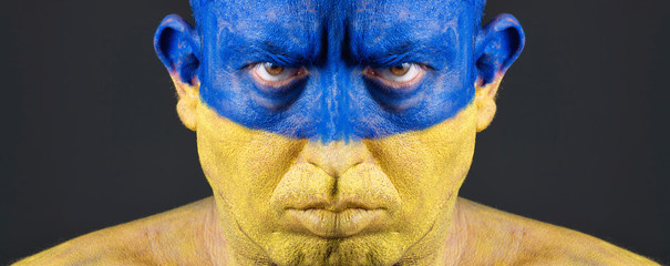 Man with his face painted with the flag of Ukraine