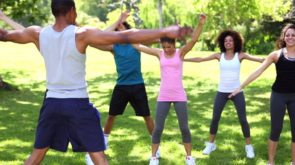 Fitness class doing jumping jacks in the park