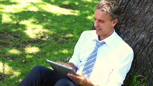 Happy businessman leaning against tree using tablet