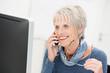 lächelnde seniorin am computer mit telefon