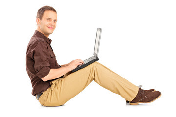 Guy working on laptop seated on the floor