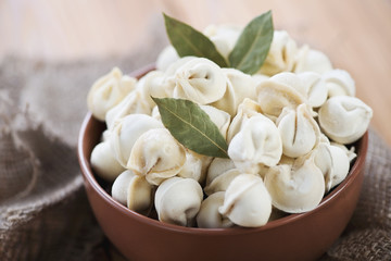Close-up of raw pelmeni with bay leaves, horizontal shot