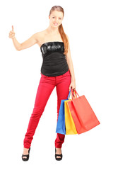 Woman with shopping bags giving thumb up