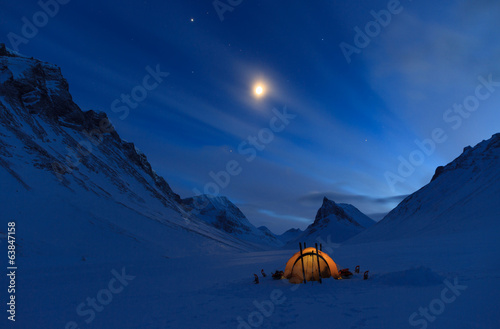 Tent in the mountains on a winter night in Lapland.