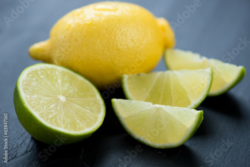Ripe lemon and sliced lime over black wooden background