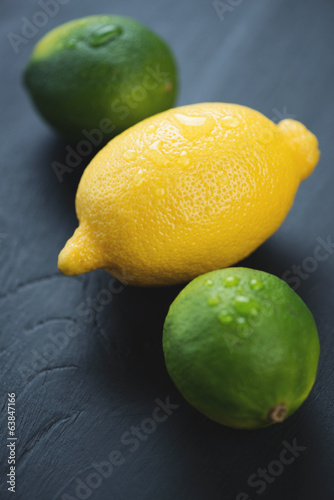 Ripe limes and lemon over black wooden surface, vertical shot