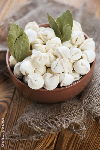 Glass bowl with raw pelmeni and dry bay leaves, vertical shot