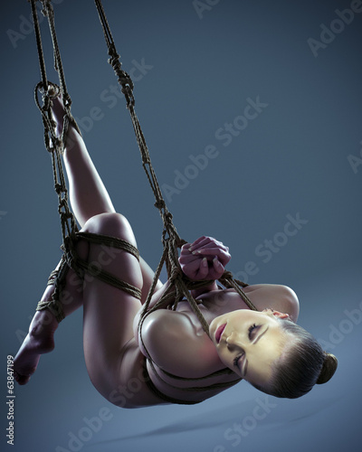 Pretty nude woman with shibari in studio