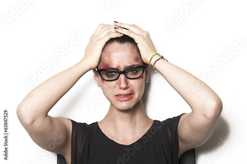 Beaten up girl wearing glasses and crying