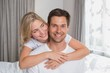 Loving woman embracing man from behind at home