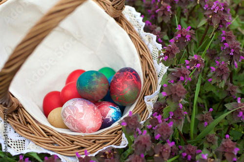 wicker basket with colorful easter eggs