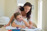 Mother assisting little daughter in homework