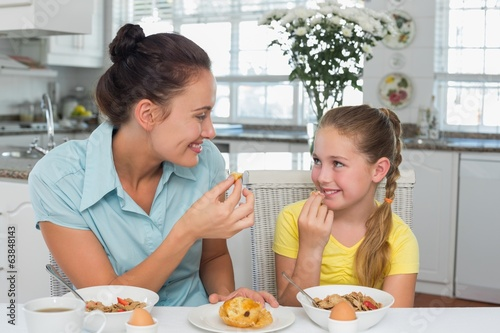 Mother and daughter having muffin at table