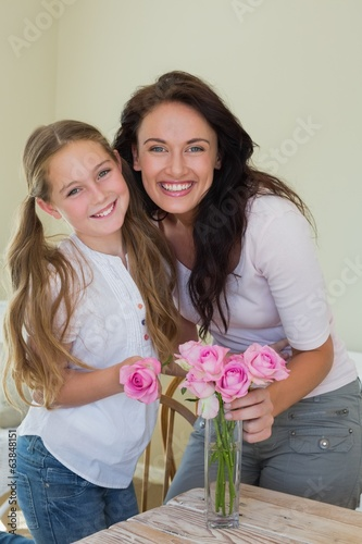 Mother and daughter arranging flowers in vase