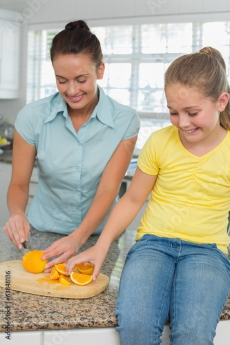Woman slicing oranges for daughter in kitchen