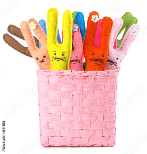 Funny handmade Easter rabbits in basket, isolated on white