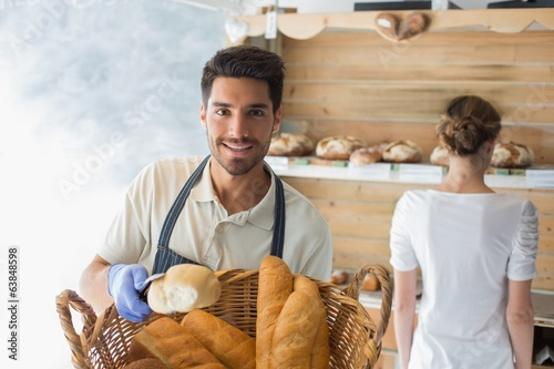 Young waiter with basket of breads at coffee shop